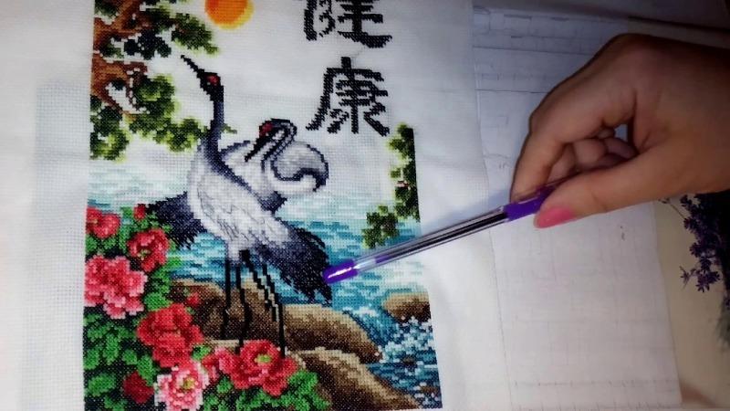 Рука вышивает птиц
